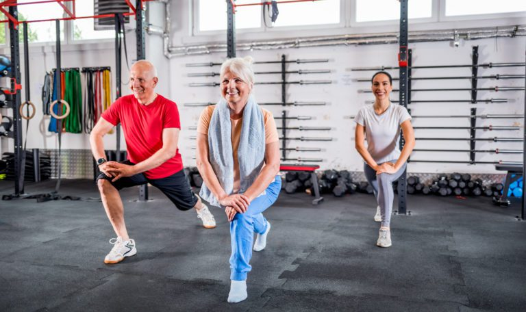 Personal Trainer mit älterem Ehepaar bei Reha-Übungen im Fitnessstudio